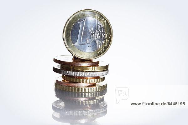 Eine Euro-Münze auf Cent-Münzenstapel