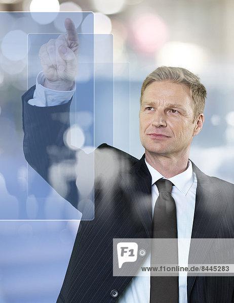 Porträt eines Geschäftsmannes  der auf eine Glasscheibe zeigt