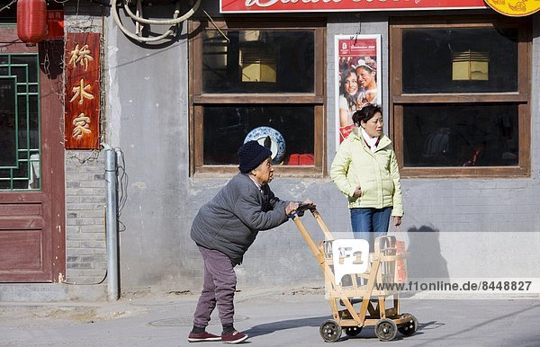 Elderly woman pushes wooden shopping cart along the pavement in the Hutongs area  Beijing  China