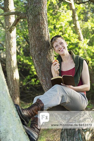 Nachdenkliche Frau mit Buch  die Apfel isst  während sie sich am Baumstamm im Wald entspannt.
