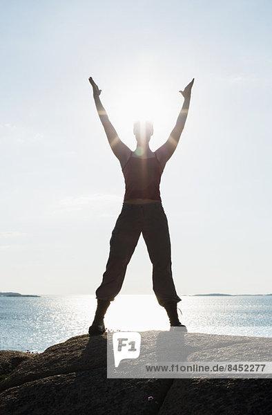 Volle Länge der Frau mit erhobenen Armen beim Yoga auf dem Felsen am Meer