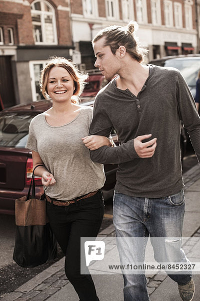 Happy couple with arm in arm walking on sidewalk