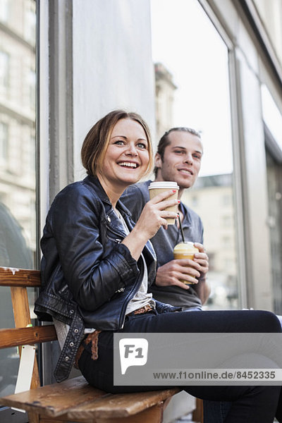 Happy couple drinking coffee in disposable cups on bench at sidewalk