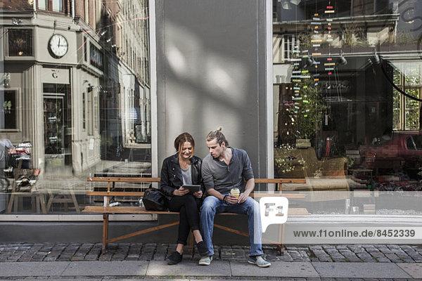 Volle Länge des Paares unter Verwendung des digitalen Tabletts zusammen auf Bürgersteigbank