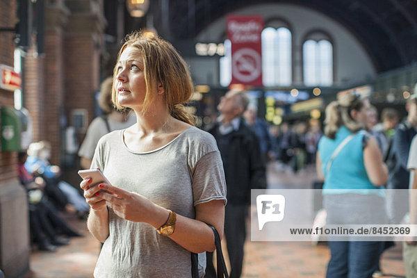 Mittlere erwachsene Frau mit Handy im Stehen auf dem Bahnhof