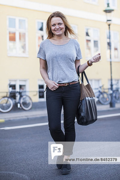Ganzflächiges Porträt einer glücklichen Frau mit Geldbörse  die auf der Straße steht.