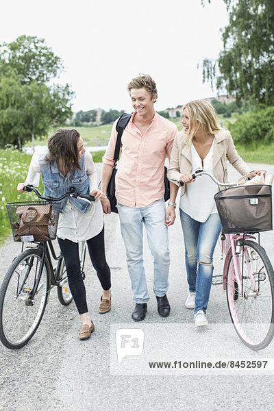 Glückliche junge Freunde mit Fahrrädern auf der Landstraße