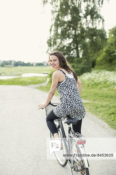 Rückansicht Porträt einer jungen Frau beim Radfahren auf der Landstraße