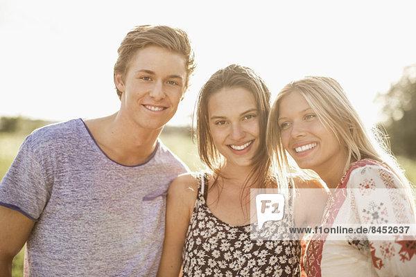 Porträt junger Freunde  die im Freien lächeln