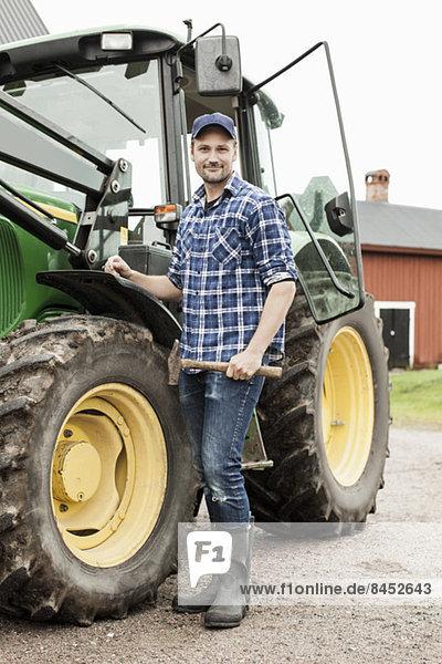 Ganzflächiges Porträt des Landwirts mit dem Hammer auf dem Bauernhof.