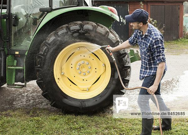 Volle Länge des mittleren erwachsenen Landwirts  der das Traktorrad mit Schlauch im Betrieb wäscht.