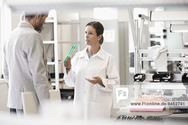 Ingenieur erklärt dem Geschäftsmann in der Fabrik das Maschinenteil