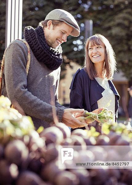 Glückliches Paar beim Gemüsekauf am Marktstand