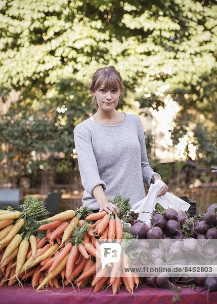 Porträt einer selbstbewussten Gemüseverkäuferin am Stand