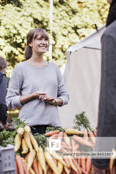 Verkäuferin verkauft Gemüse auf dem Markt