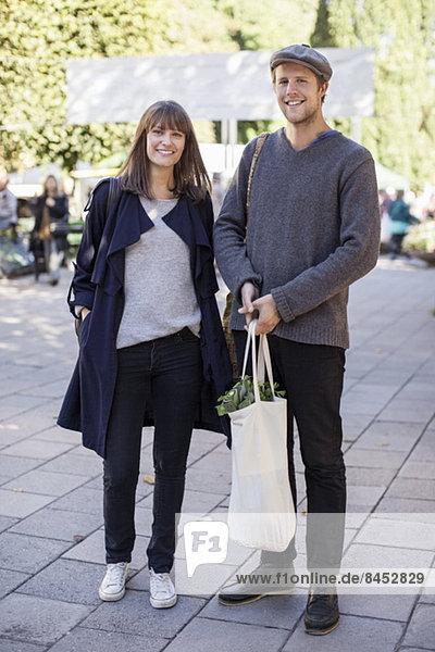 Volle Länge des Paares mit Einkaufstasche auf dem Bürgersteig