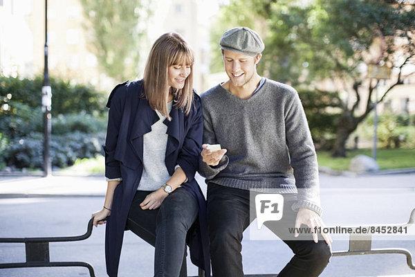 Junges Paar mit Handy im Freien