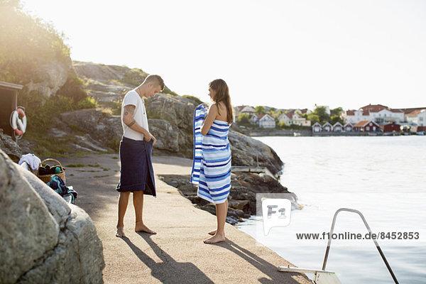 Volle Länge des Paares  das sich am Seeufer in ein Handtuch wickelt.
