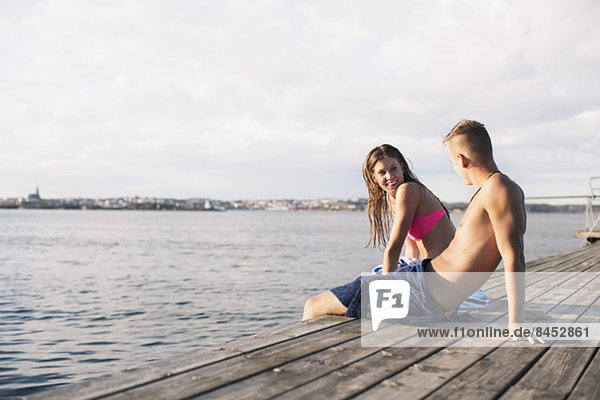 Young couple sitting at wooden pier
