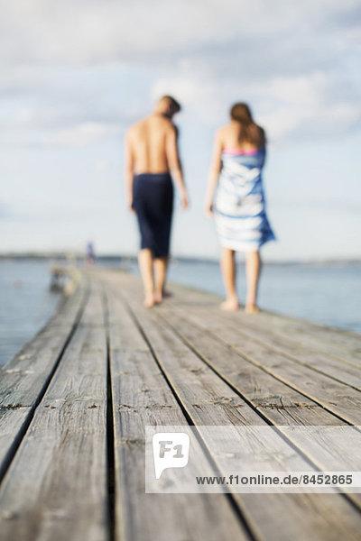 Paar in Handtücher gehüllt auf einem hölzernen Steg
