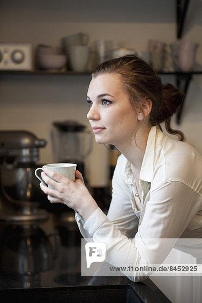 Nachdenkliche Frau mit Kaffeetasse schaut weg und lehnt sich an die Küchenzeile.
