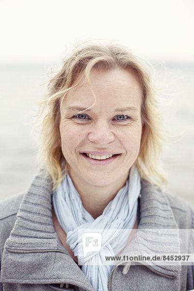 Porträt einer glücklichen Frau am Seeufer