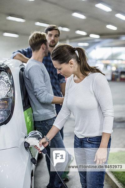 Frau lädt Elektroauto mit Freunden  die im Hintergrund an der Tankstelle stehen.