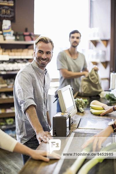 Lächelnder Mann an der Supermarktkasse mit Freund im Hintergrund