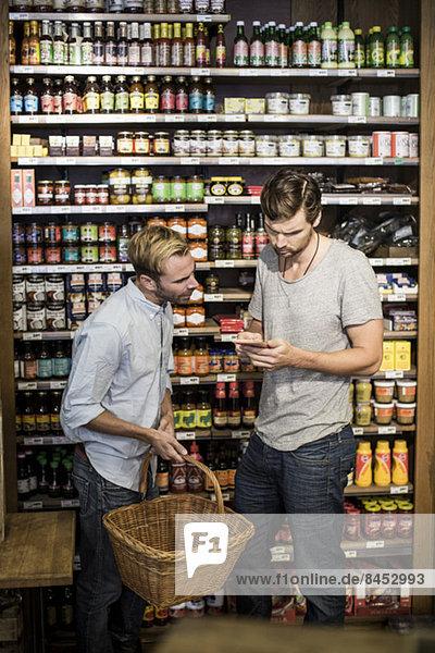 Junge männliche Freunde lesen Etikett gegen Regal im Supermarkt