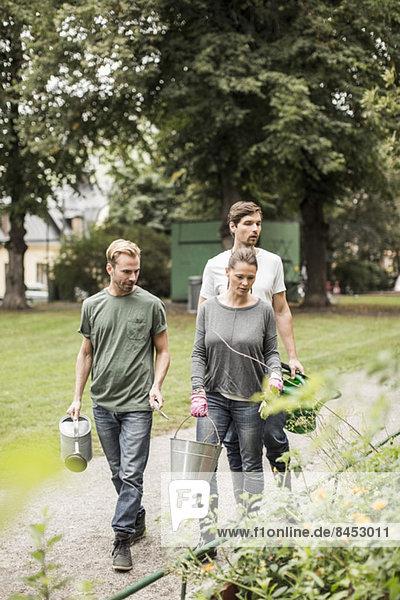 Freunde mit Gartengeräten beim Spaziergang durch den Garten