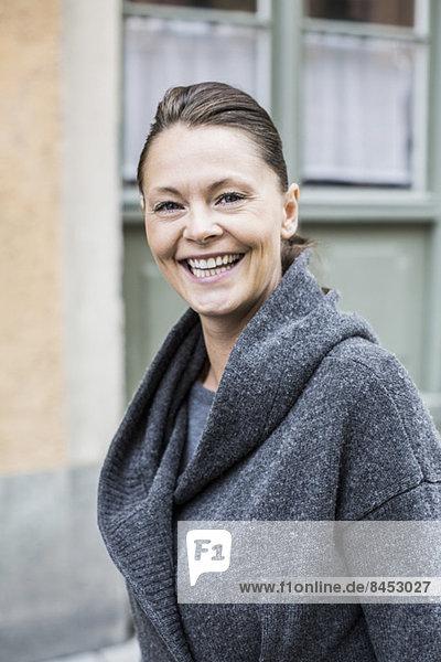 Porträt einer glücklichen Frau in warmer Kleidung im Freien