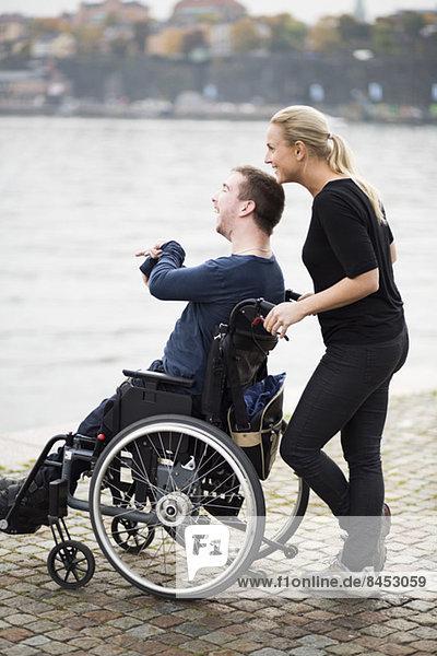 Glücklicher behinderter Mann mit Hausmeister mit Seeblick