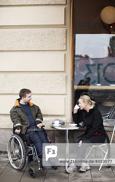 Hausmeisterin und behinderter Mann beim Kaffeetrinken im Straßencafé