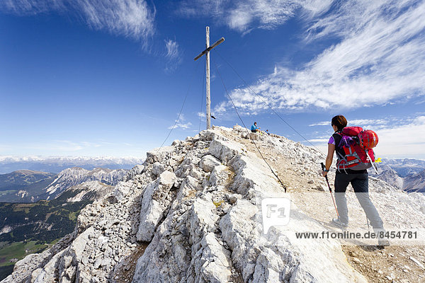 Bergsteiger am Gipfelkreuz des Heiligkreuzkofel in der Fanesgruppe im Naturpark Fanes-Sennes-Prags  unten das Gadertal  Alta Badia  Dolomiten  Südtirol  Italien