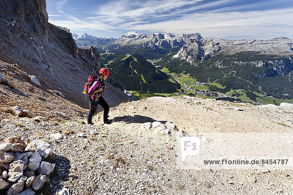 Bergsteigerin auf der Kreuzkofelscharte beim Aufstieg auf den Heiligkreuzkofel über den Heiligkreuzkofelsteig im Naturpark Fanes-Sennes-Prags  unten das Gadertal und Abtei  hinten der Sellastock und die Puezgruppe  Dolomiten  Südtirol  Italien