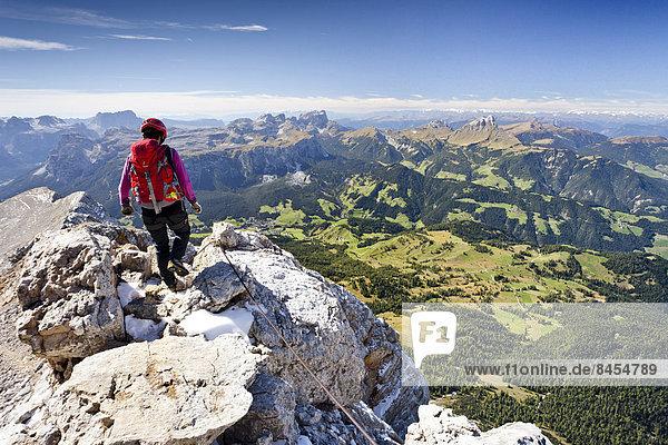 Bergsteiger beim Abstieg von der Zehnerspitze über die Zehner-Ferrata in der Fanesgruppe im Naturpark Fanes-Sennes-Prags  Ausblick auf das Gadertal  die Puezgruppe und den Sellastock  Dolomiten  Südtirol  Italien