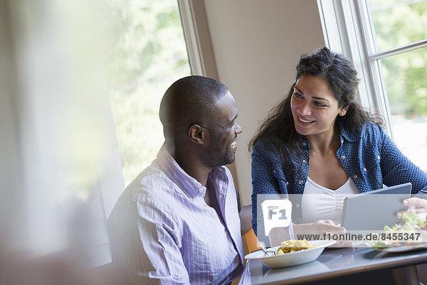 Ein Paar sitzt und schaut auf ein digitales Tablett.