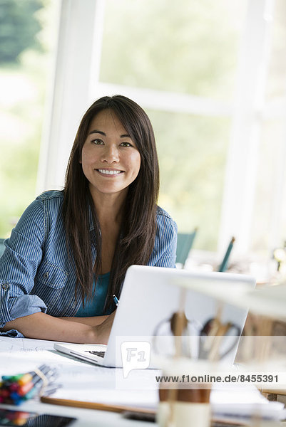 A woman in an office  working at a laptop computer.
