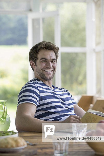 A man sitting at a table reading a book.