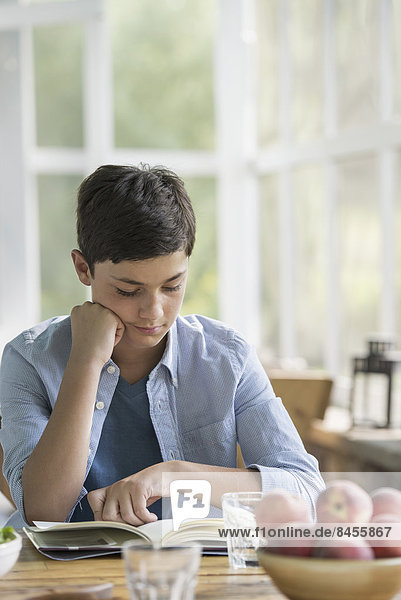 A young boy sitting reading a book.