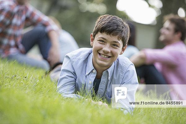 Ein Junge sitzt auf dem Rasen  bei einem Sommerfest.