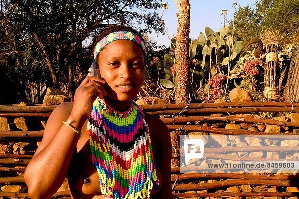 Colorful Woman with Cell Phone in Native Zulu Tribe at Shakaland Center South Africa.