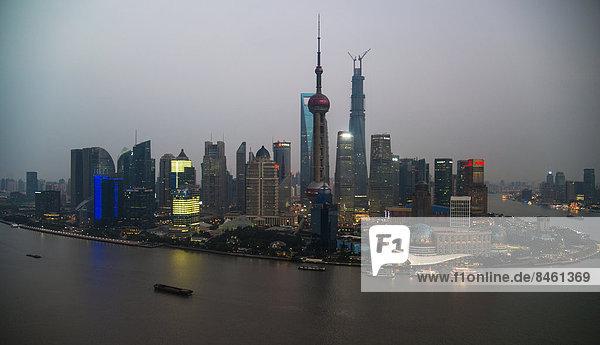 Skyline Finanzviertel mit Oriental Pearl Tower  Shanghai Tower  Pudong mit Fluss Huangpu in der Abenddämmerung  Shanghai  China