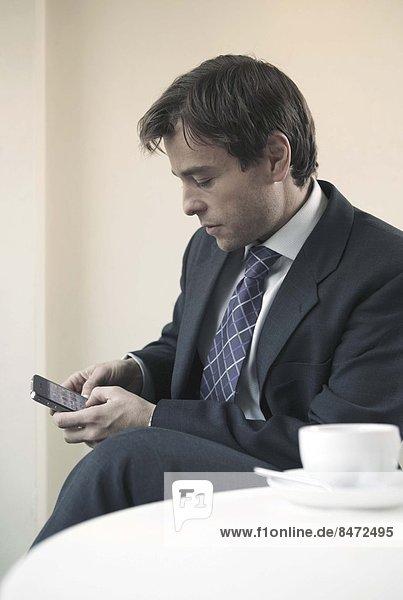 sitzend  benutzen  Geschäftsmann  Tisch  Smartphone