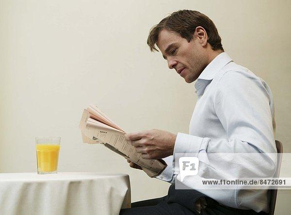 sitzend  Geschäftsmann  Finanzen  Tisch  Zeitung  vorlesen