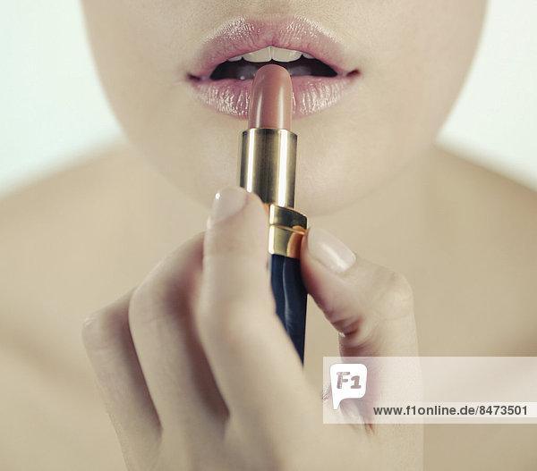 Eine junge Frau Anwendung Lippenstift