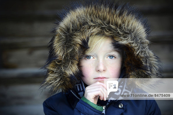 Boy  7 years  with a fur hood  pensive  portrait