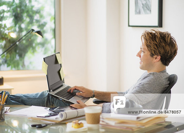 Mann mit Laptop im home-office Heimarbeitsplatz
