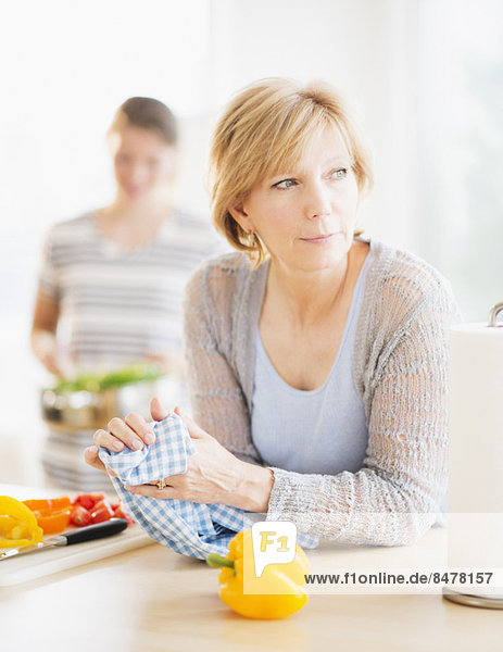 Mother leaning on kitchen counter  out-of-focus daughter in background