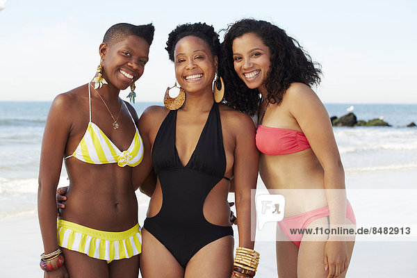 Women smiling together on beach